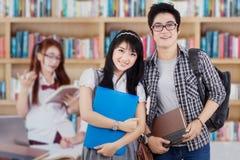 Studente di college due con il gruppo in biblioteca Immagini Stock