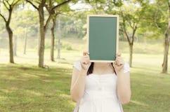Studente di college femminile asiatico che tiene lavagna in bianco Fotografia Stock