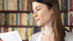 Studente di college femminile in biblioteca con i manuali Primo giorno del banco Scaffali per libri nel fondo video d archivio