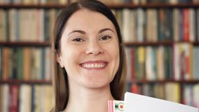 Studente di college femminile in biblioteca con i manuali Primo giorno del banco Scaffali per libri nel fondo stock footage
