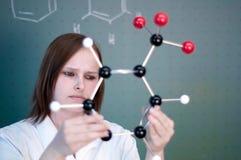 Studente di college femminile che esamina un modello chimico Immagini Stock