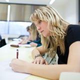 Studente di college femminile che si siede in un'aula Immagine Stock Libera da Diritti