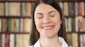 Studente di college femminile che sorride nella biblioteca Primo giorno del banco Scaffali per libri dello scaffale nel fondo stock footage