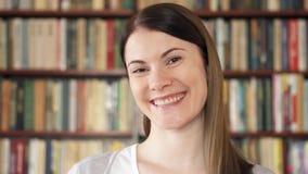 Studente di college femminile che sorride nella biblioteca Primo giorno del banco Scaffali per libri dello scaffale nel fondo video d archivio