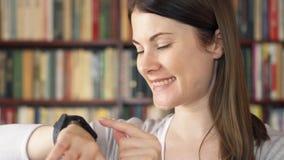 Studente di college femminile che utilizza orologio astuto nella biblioteca, passando in rassegna, leggendo, chiacchierando con g stock footage