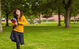 Studente di college femminile con i libri che corre nel parco Fotografie Stock Libere da Diritti