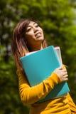 Studente di college femminile con i libri in parco Fotografia Stock Libera da Diritti