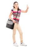 Studente di college femminile con una borsa di spalla che dà un pollice su Fotografia Stock