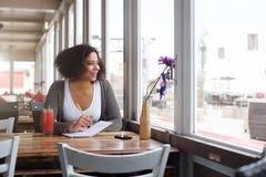 Studente di college femminile felice che si siede al ristorante con il blocco note Fotografia Stock Libera da Diritti