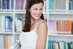 Studente di college femminile grazioso nella libreria Immagine Stock