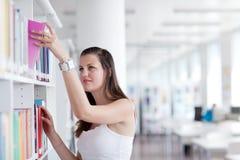 Studente di college femminile grazioso nella libreria Immagine Stock Libera da Diritti