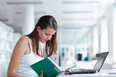 Studente di college femminile grazioso nella libreria Fotografia Stock Libera da Diritti