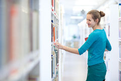 Studente di college femminile grazioso in una libreria Immagine Stock