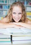 Studente di college femminile grazioso in una libreria Fotografie Stock