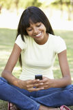 Studente di college femminile Sitting In Park che per mezzo del telefono cellulare Fotografia Stock