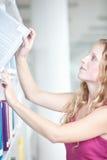 Studente di college femminile in una libreria Fotografia Stock Libera da Diritti