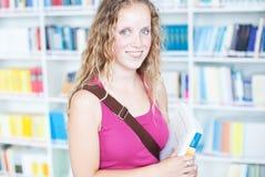 Studente di college femminile in una libreria Immagine Stock