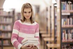 Studente di college femminile in una libreria Immagini Stock Libere da Diritti
