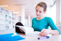Studente di college femminile in una libreria Immagini Stock