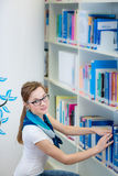 Studente di college grazioso e femminile in una biblioteca Fotografia Stock Libera da Diritti