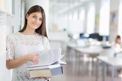 Studente di college grazioso e giovane che cerca un libro nel ibrary Fotografie Stock