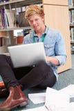 Studente di college maschio Studying In Library con il computer portatile Immagini Stock