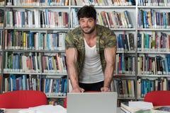 Studente di college muscolare in una biblioteca Fotografia Stock Libera da Diritti
