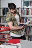 Studente di college muscolare in una biblioteca Fotografia Stock