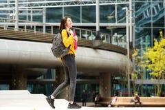 Studente di college sorridente che cammina sulla città universitaria dell'istituto universitario con la borsa Immagine Stock