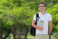Studente di college sorridente con lo zaino che tiene una compressa Immagini Stock Libere da Diritti