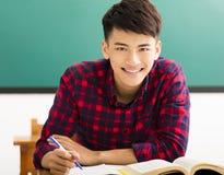 Studente di college sorridente nell'aula dell'università Fotografia Stock
