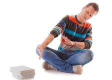 Studente di college stanco con la pila di libri che studia per gli esami isolati Immagini Stock
