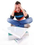 Studente di college stanco con la pila di libri isolati Immagine Stock