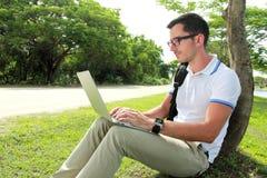Studente di Colllege che lavora alle assegnazioni facendo uso del computer portatile Immagine Stock Libera da Diritti
