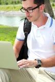 Studente di Colllege che lavora alle assegnazioni facendo uso del computer portatile Fotografia Stock Libera da Diritti