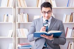 Studente di diritto di affari con la lente d'ingrandimento che legge un libro Immagini Stock Libere da Diritti