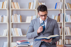 Studente di diritto di affari con la lente d'ingrandimento che legge un libro Fotografia Stock Libera da Diritti