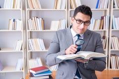 Studente di diritto di affari con la lente d'ingrandimento che legge un libro Fotografie Stock