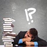 Studente di diritto stanco che esamina un grande mucchio dei libri Immagine Stock