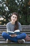 Studente di felicità che si siede sul banco di legno con il libro blu, all'aperto Immagini Stock