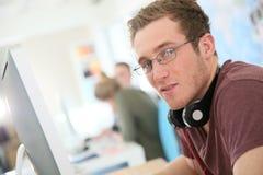 Studente di informatica con gli occhiali davanti al desktop Fotografie Stock Libere da Diritti