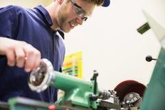Studente di ingegneria che per mezzo del macchinario pesante Fotografie Stock