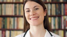 Studente di medicina femminile in biblioteca pronta per la preparazione degli esami finali Scaffali per libri nei precedenti stock footage