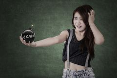 Studente di panico che tiene una bomba con il testo dell'esame Fotografia Stock