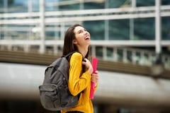 Studente di risata che cammina con la borsa ed i libri sulla città universitaria Fotografia Stock