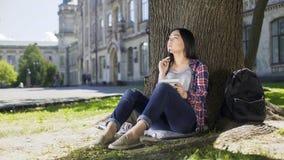 Studente di scambio che si siede sotto l'albero, tenendo taccuino, pensante sul progetto Fotografia Stock Libera da Diritti