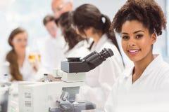 Studente di scienza che guarda tramite il microscopio in laboratorio Immagine Stock Libera da Diritti