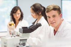 Studente di scienza che guarda tramite il microscopio in laboratorio Fotografia Stock Libera da Diritti