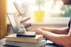 Studente di scienza che impara a casa con i libri ed il computer portatile Fotografia Stock