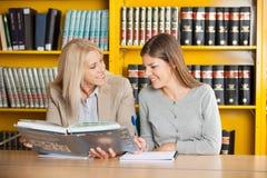 Studente di spiegazione In di Holding Book While dell'insegnante Immagine Stock Libera da Diritti